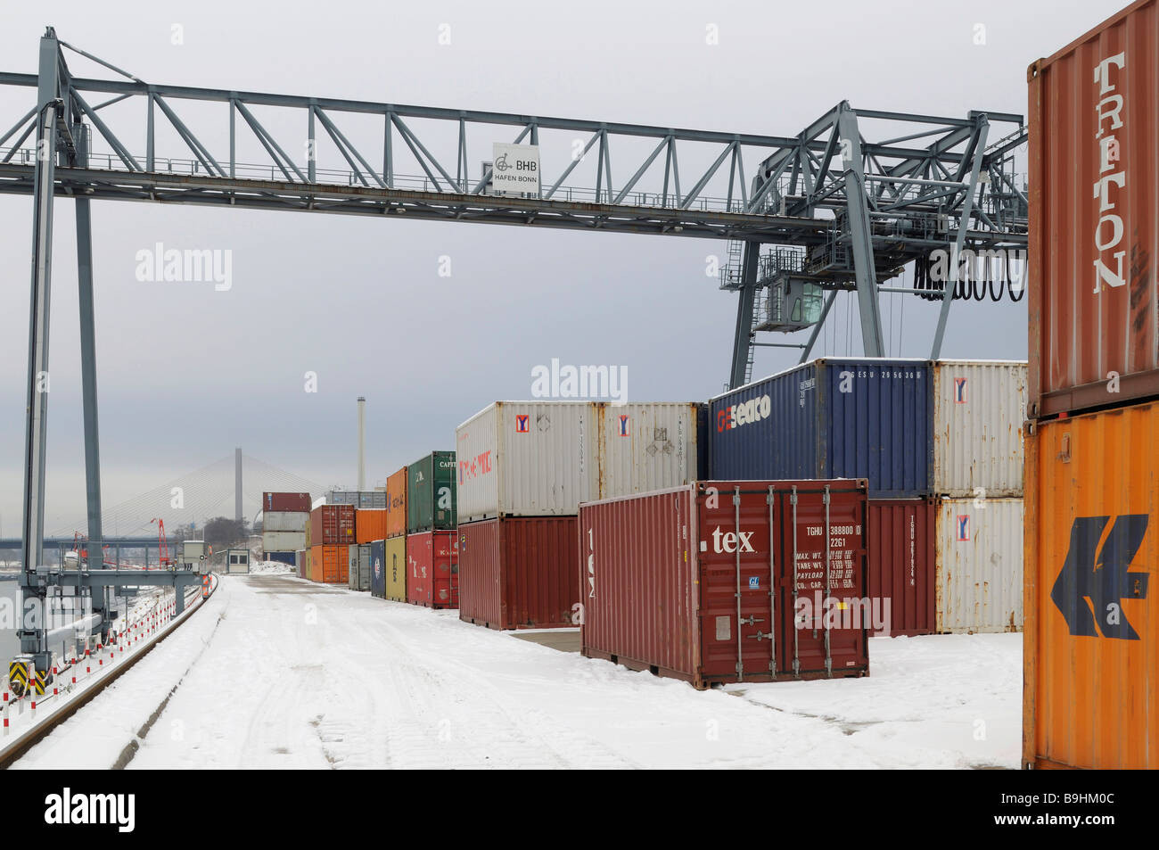 Winter at Bonn Harbour, snow-covered quay, view of container terminal and portainer, North Rhine-Westphalia, Germany, - Stock Image