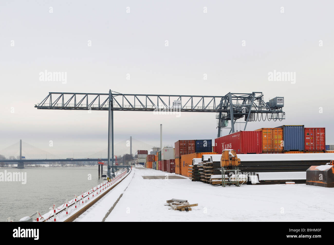 Winter at Bonn Harbour, snow-covered quay, view of container terminal and portainer on the Rhine river, North Rhine - Stock Image