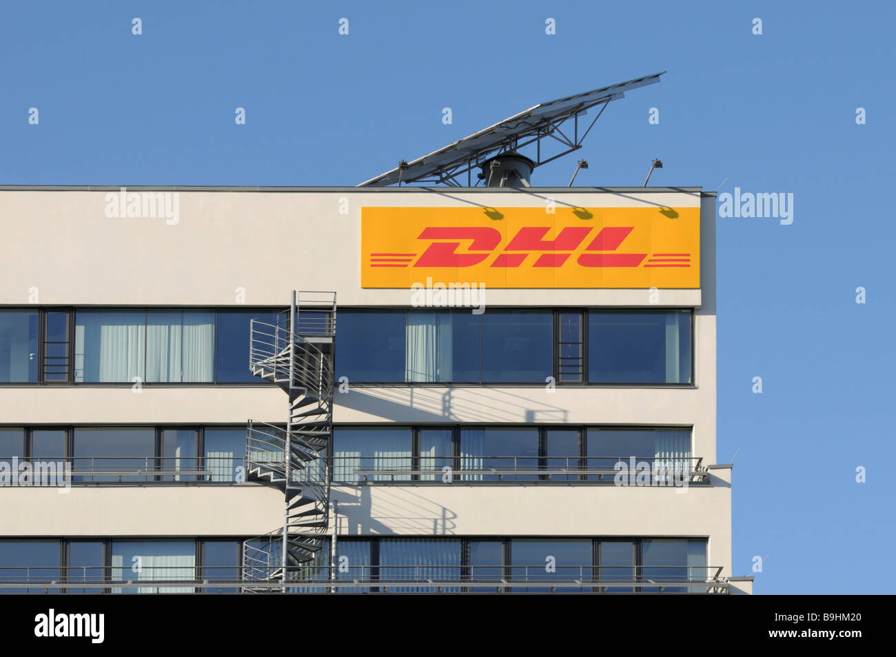 DHL logo on an office building, above it a mobile solar module, built-on fire stairs Stock Photo