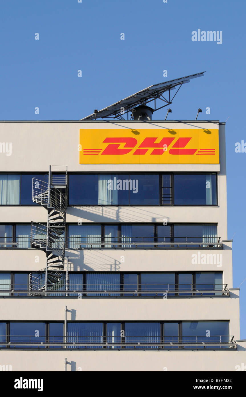 DHL logo on an office building, above it a mobile solar module, built-on fire stairs - Stock Image