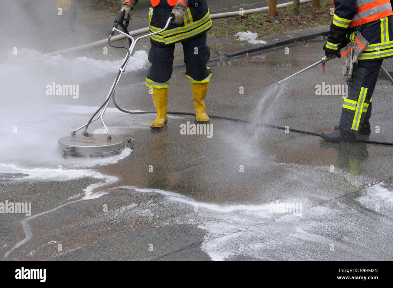 Fire brigade in action, neutralising leaked brake fluid with cleaning equipment and water nozzles - Stock Image