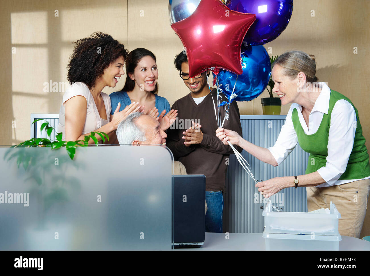 Group of people celebrating co-worker - Stock Image