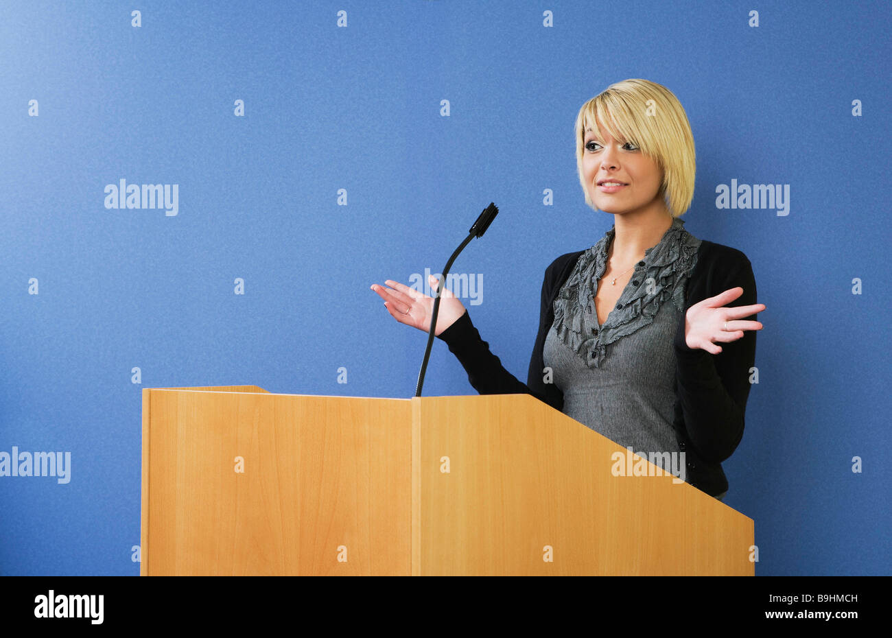 Woman talking from lectern - Stock Image
