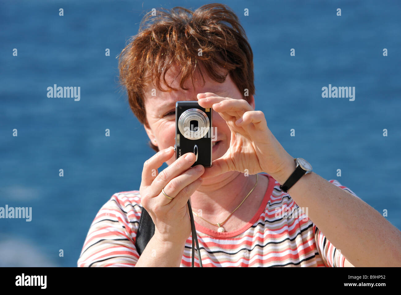Woman taking a picture with a Lumix digital camera - Stock Image