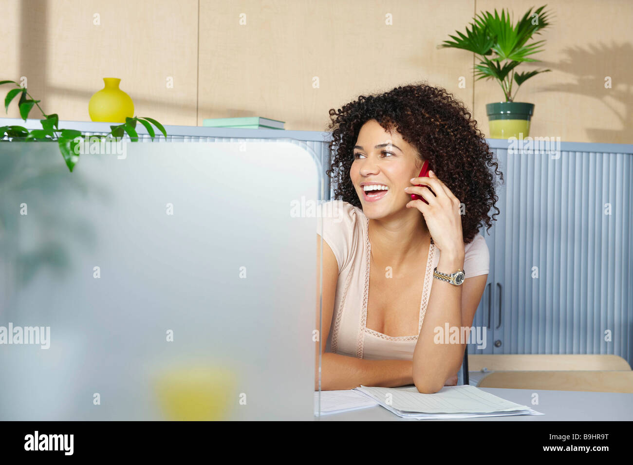Young woman on phone at desk in office - Stock Image