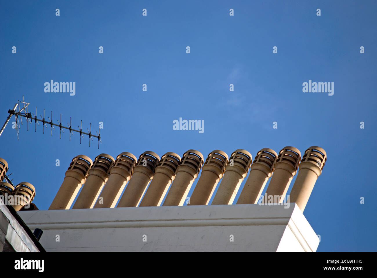 row of chimneys against a blue sky on a residential building near belgrave square, london, england - Stock Image