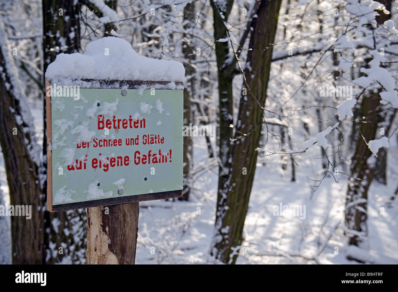 Sign covered in snow, warning of snow and ice - Stock Image