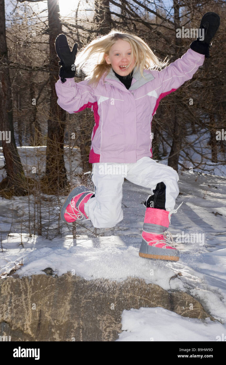 Girl Jumping wearing ski outfit - Stock Image
