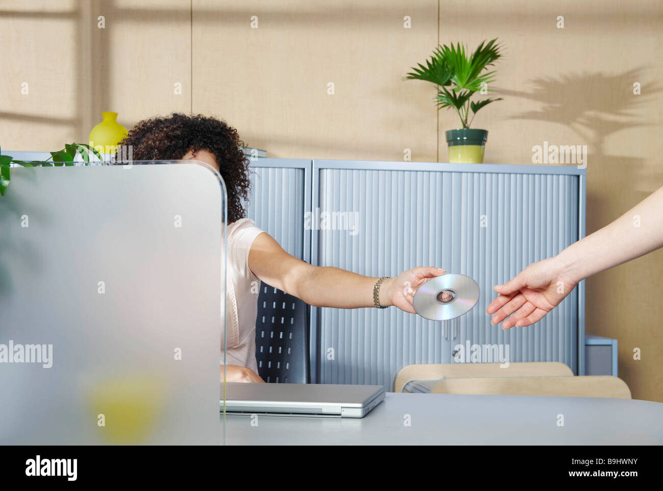 Woman handing over DVD to co-worker - Stock Image