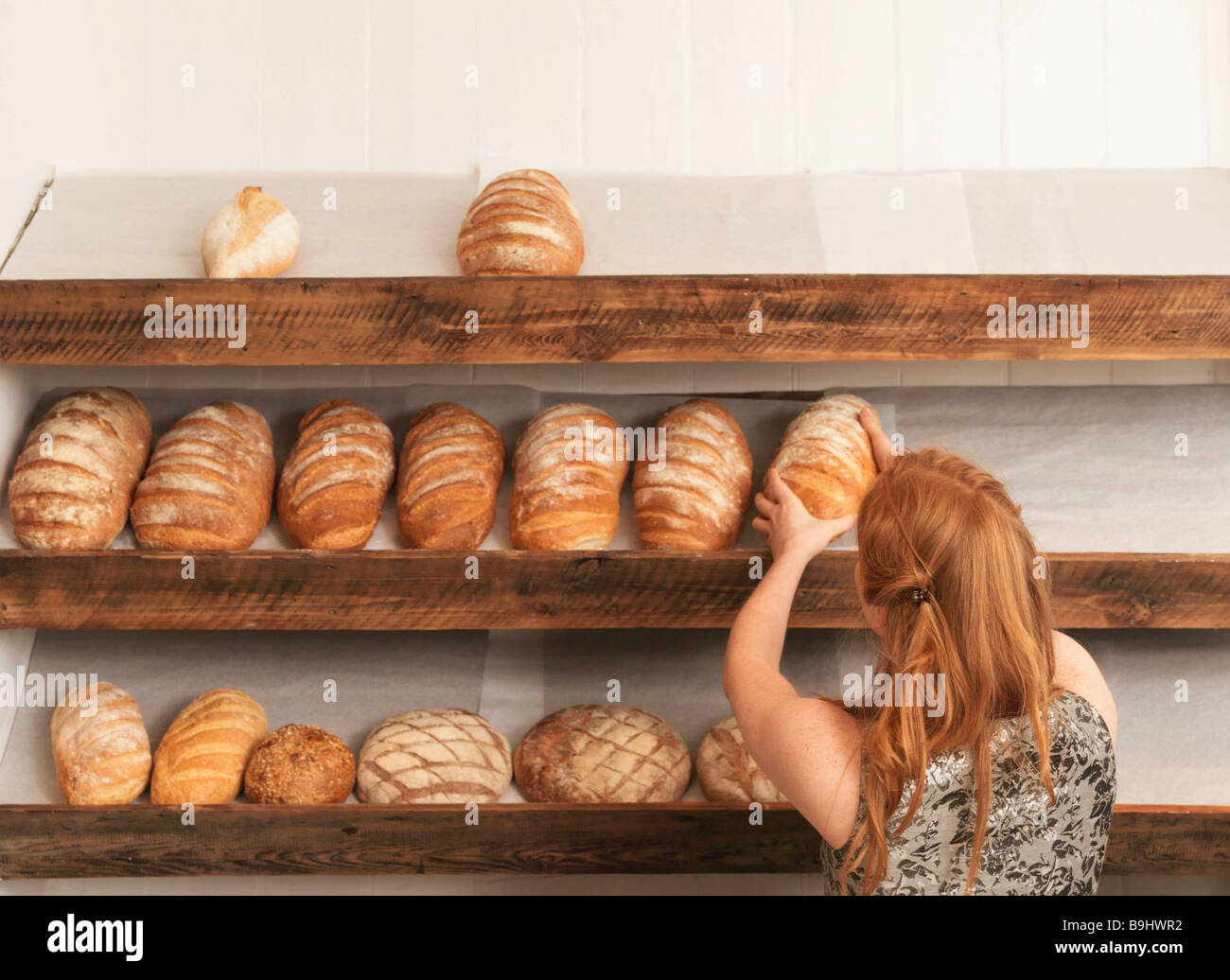 Woman stocking shelves in bakery - Stock Image