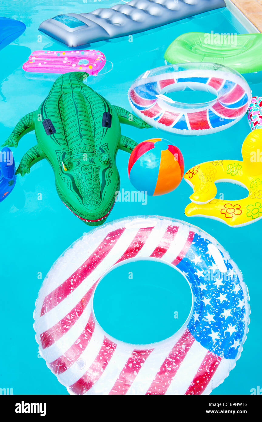 Air mattresses floating on swimming pool - Stock Image