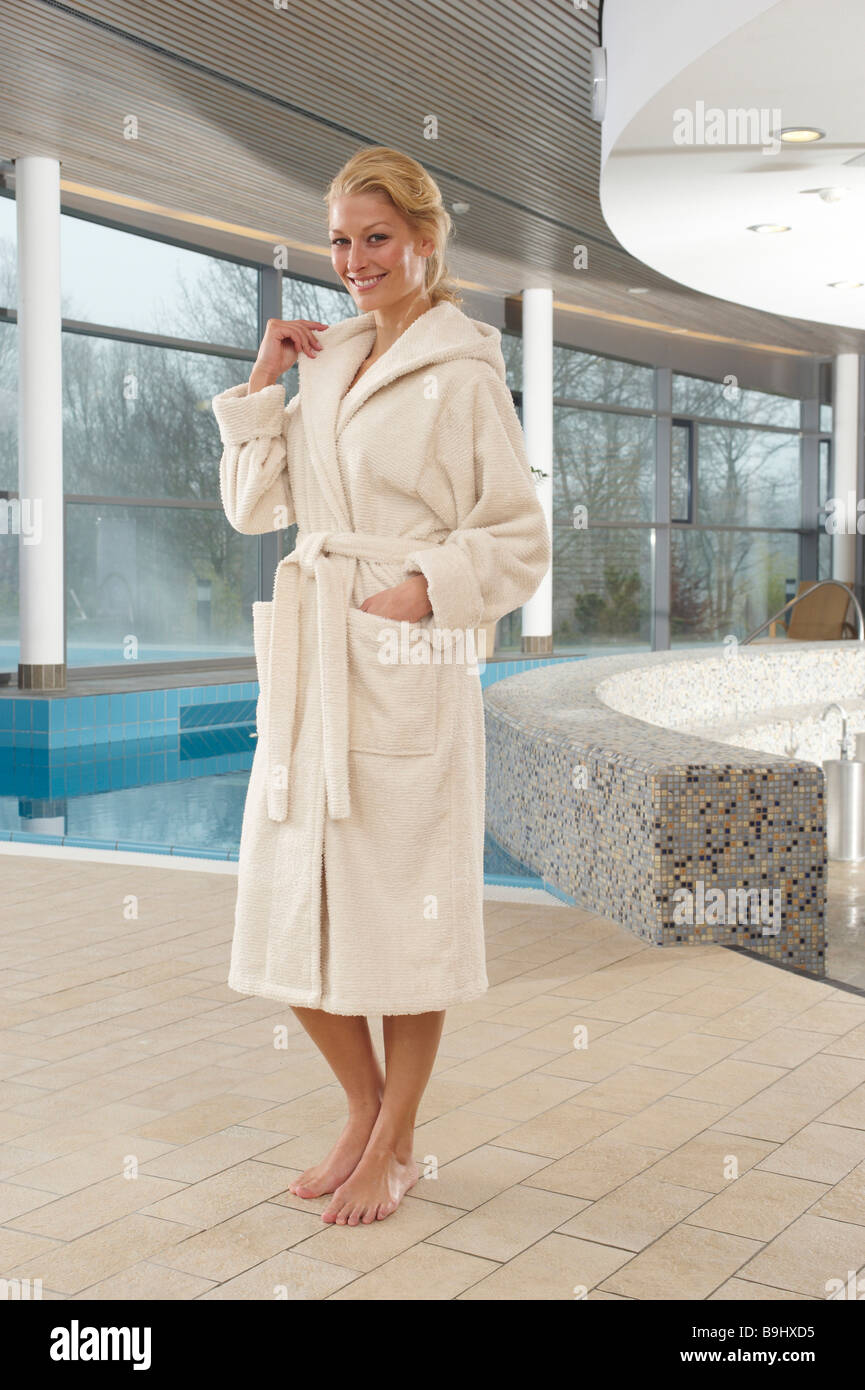 Woman wearing a terry cloth robe in the wellness area of a sauna ... e267b277c
