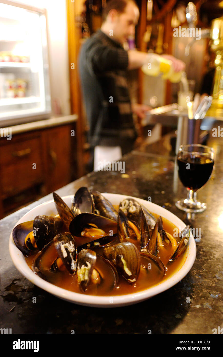 Bowl of mussels in spicy reddy brown watery soup which is a speciality tapa of Bar PIlar in El Carmen Valencia Spain - Stock Image