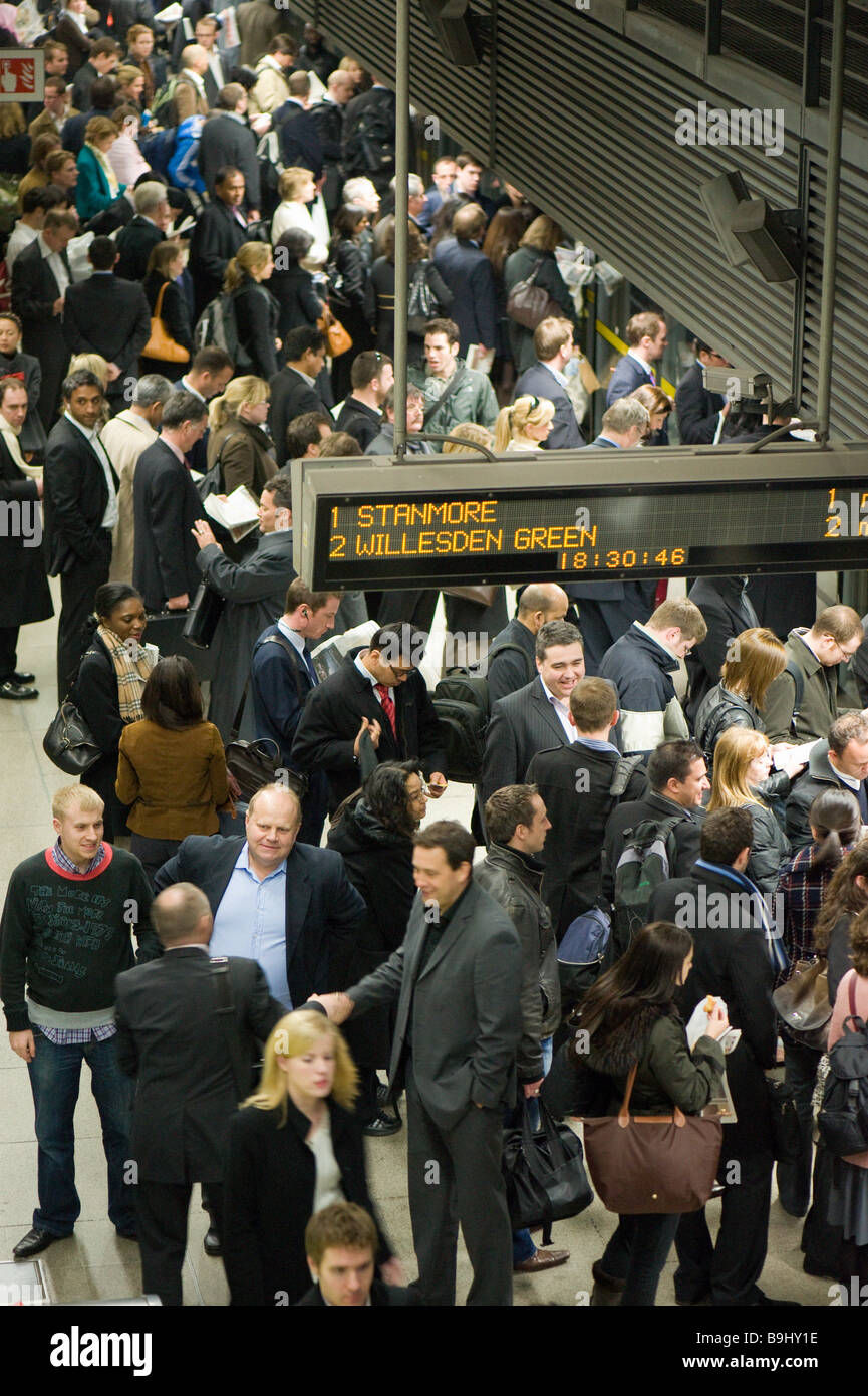 Commuters on crowded platform awaiting train Canary Wharf Docklands London United Kingdom - Stock Image
