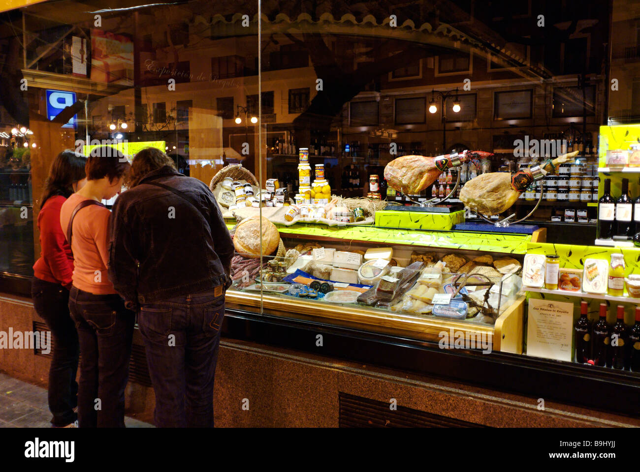 People window shopping at Spanish gourmet delicatessen food shop in the historical city centre of Valencia Spain - Stock Image