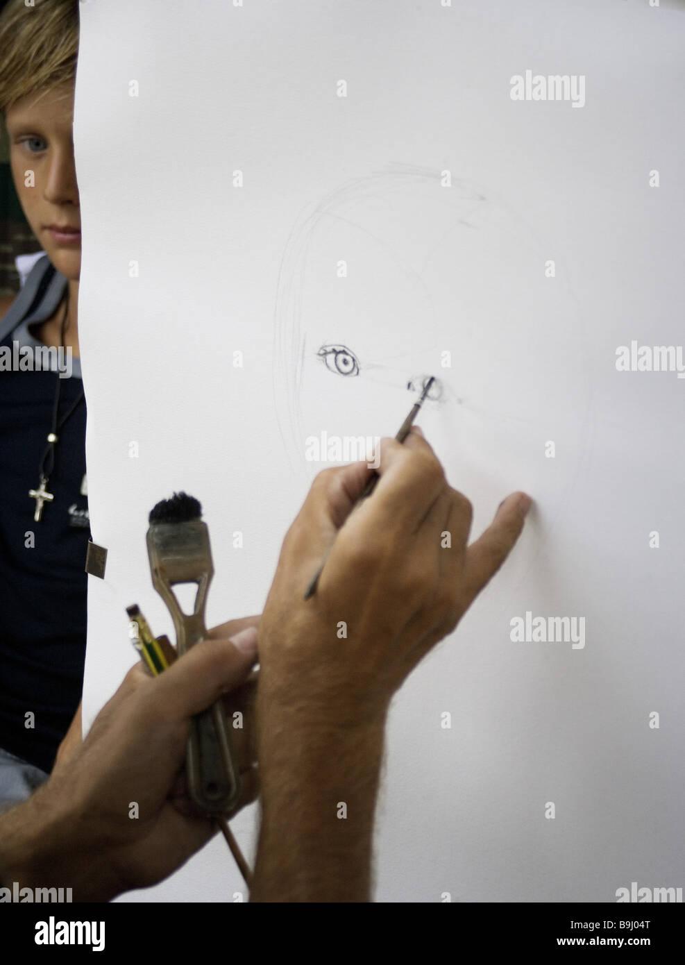 Artists canvas boy portrays broached series art hands men's-hands utensils brushes pencils paper sketch paintings - Stock Image