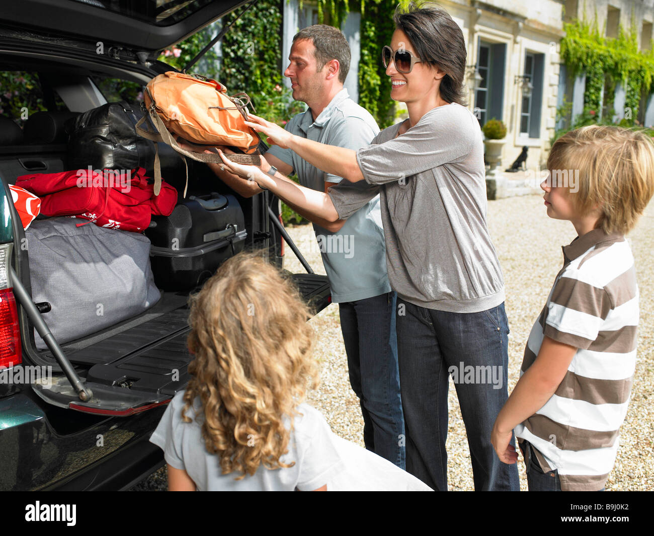 Family charging bags in the trunk - Stock Image