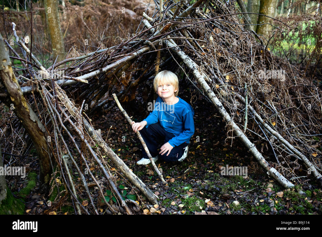Boy in hut made of Tree branches - Stock Image