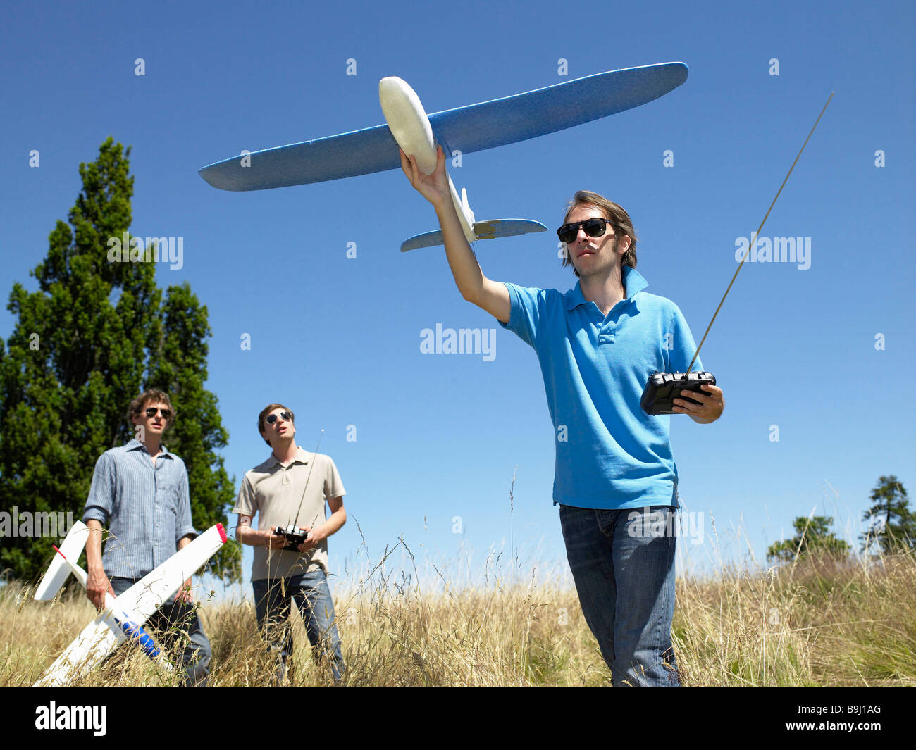 Men playing with remote-controlled plane - Stock Image