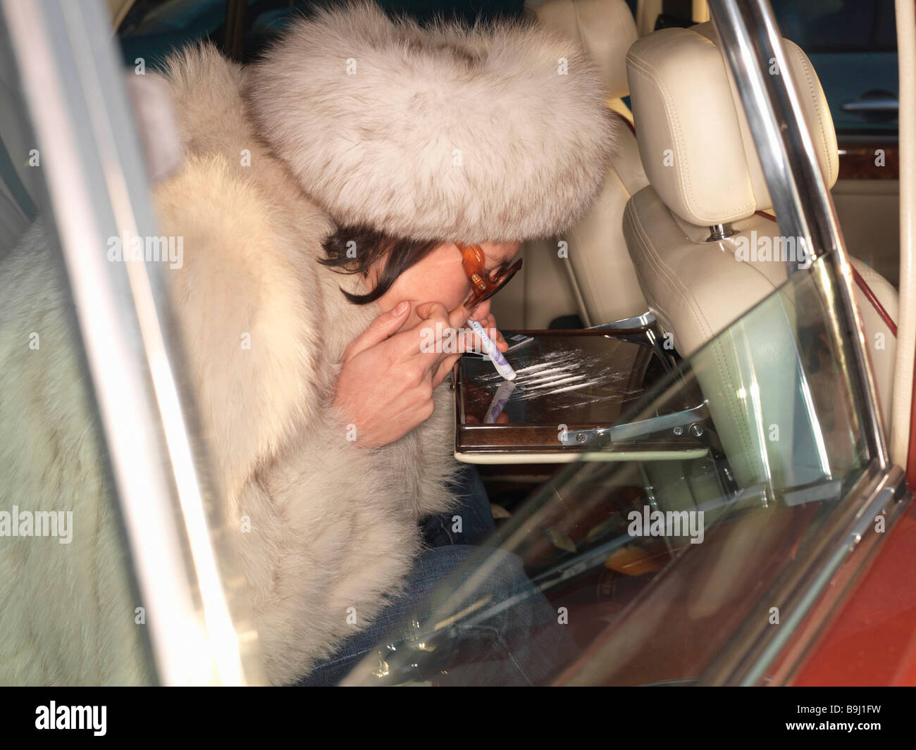 Woman snorting cocaine in luxury car - Stock Image