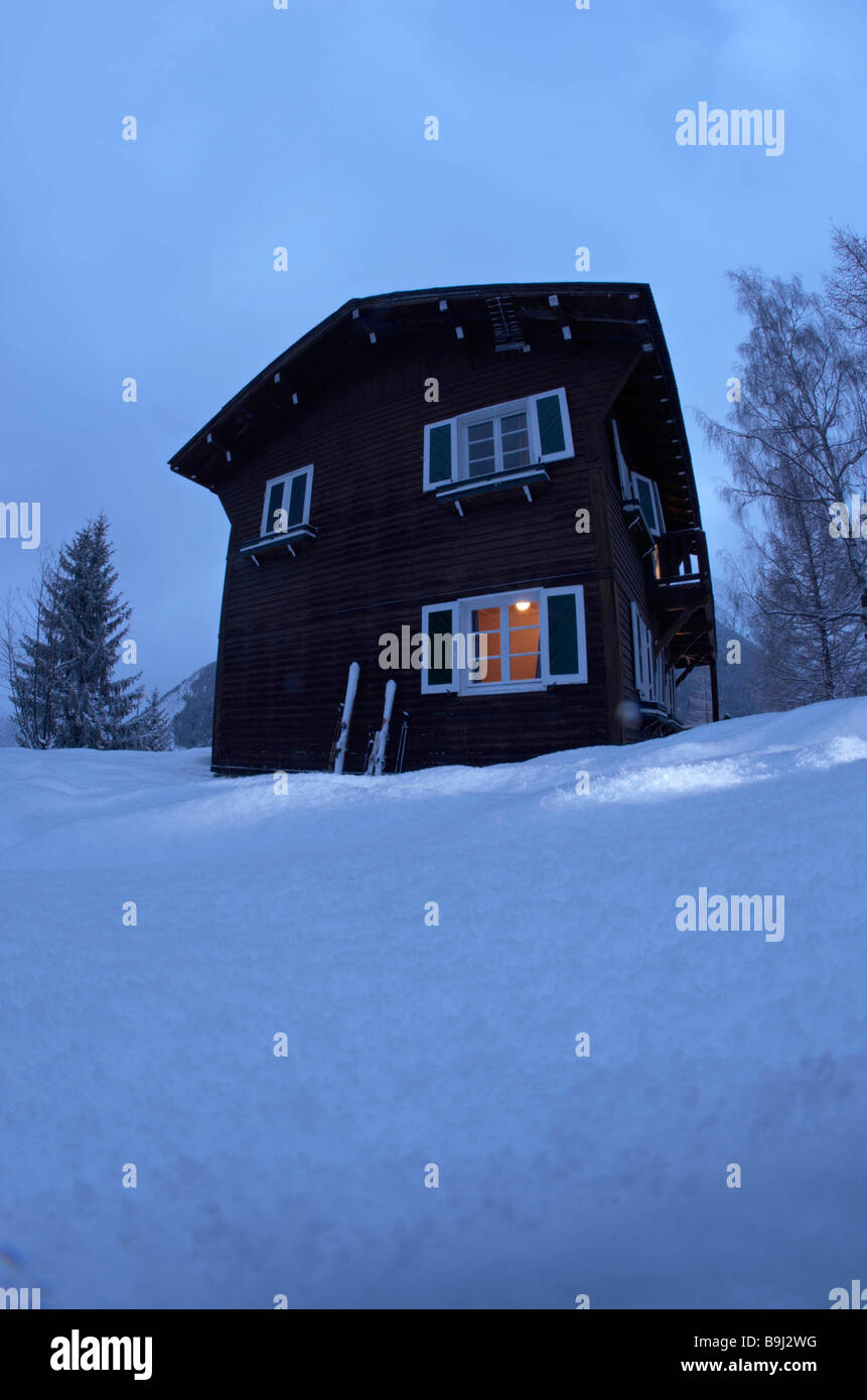 Chalet with light inside,  at dusk - Stock Image