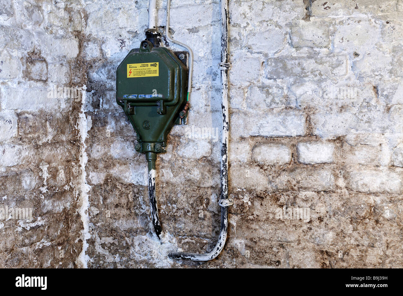 House connection, current 330 V with fuse panel 63 A in a house cellar before renovation, damp walls, Germany, Europe - Stock Image