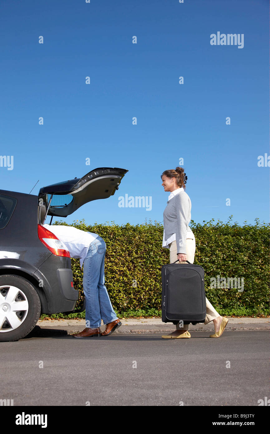 Couple putting bags into car - Stock Image