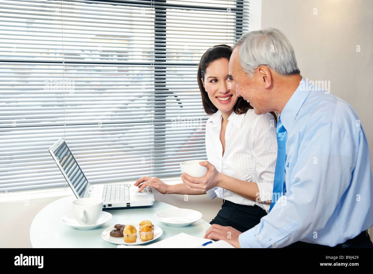 Co-workers in cafe with laptop smiling - Stock Image