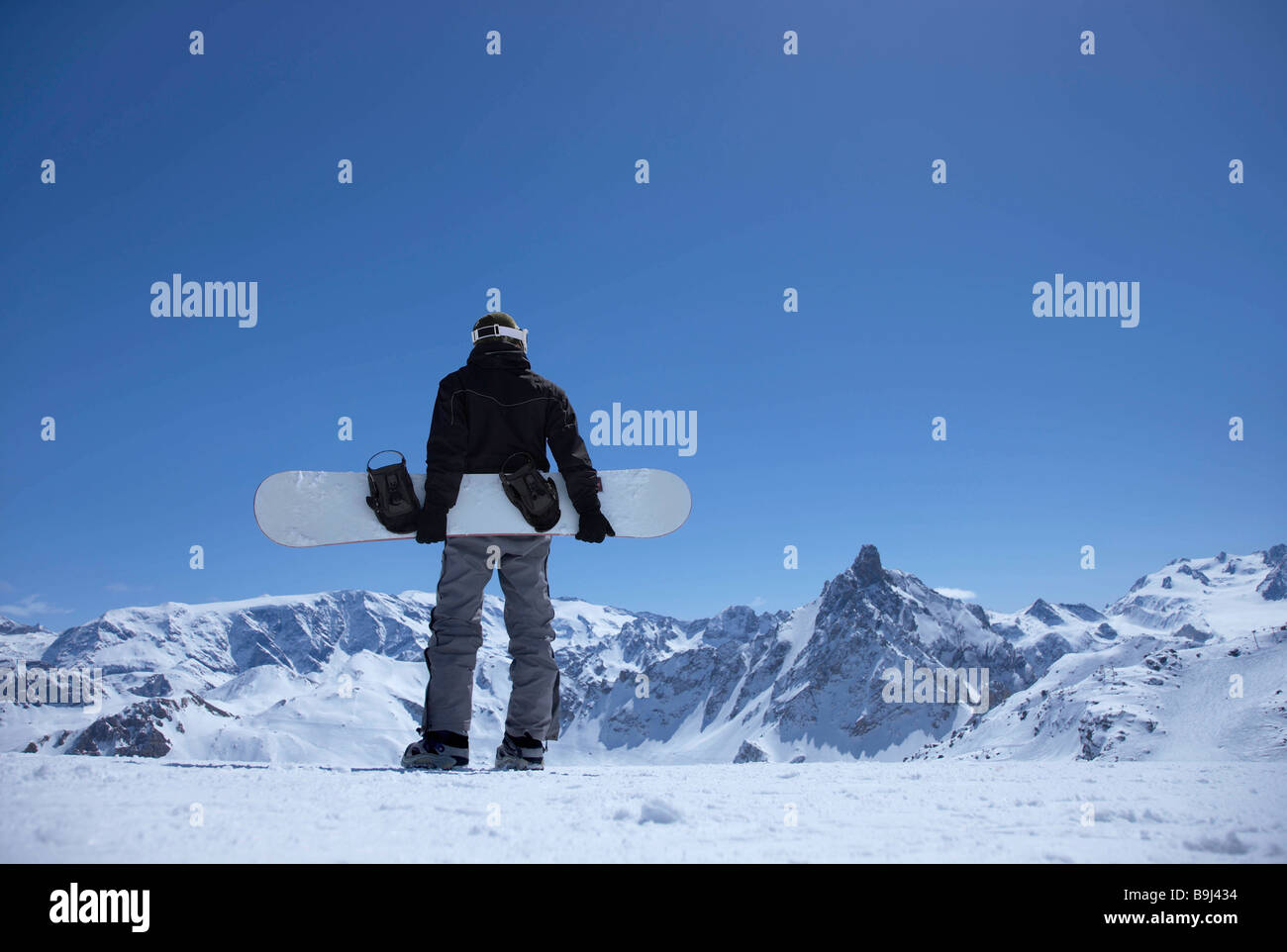 Man standing on mountain with snowboard - Stock Image