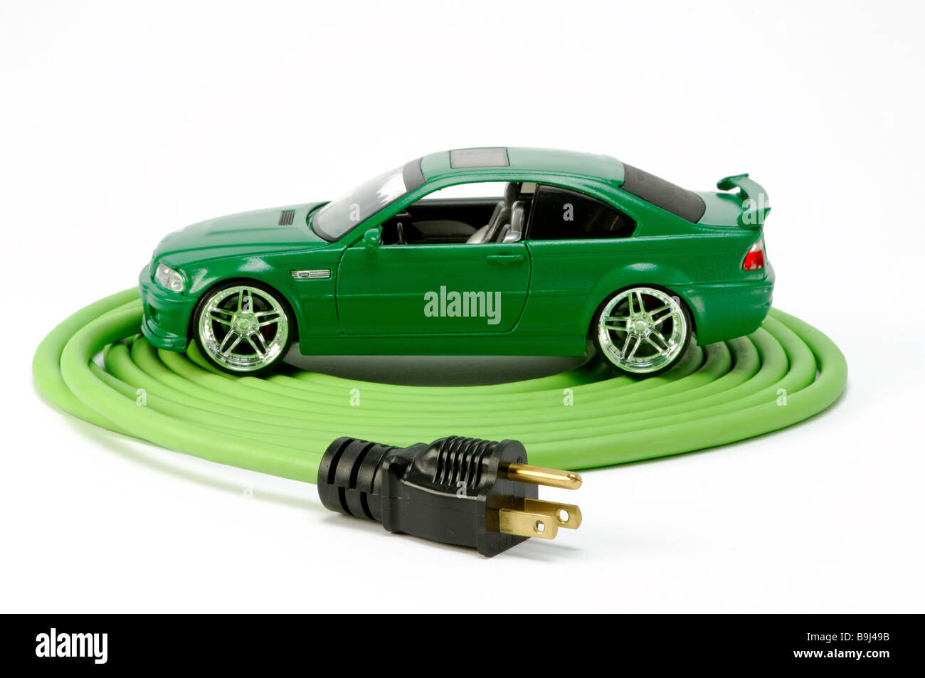 A green automobile car on a green coiled electrical extension power cord with one plug - Stock Image