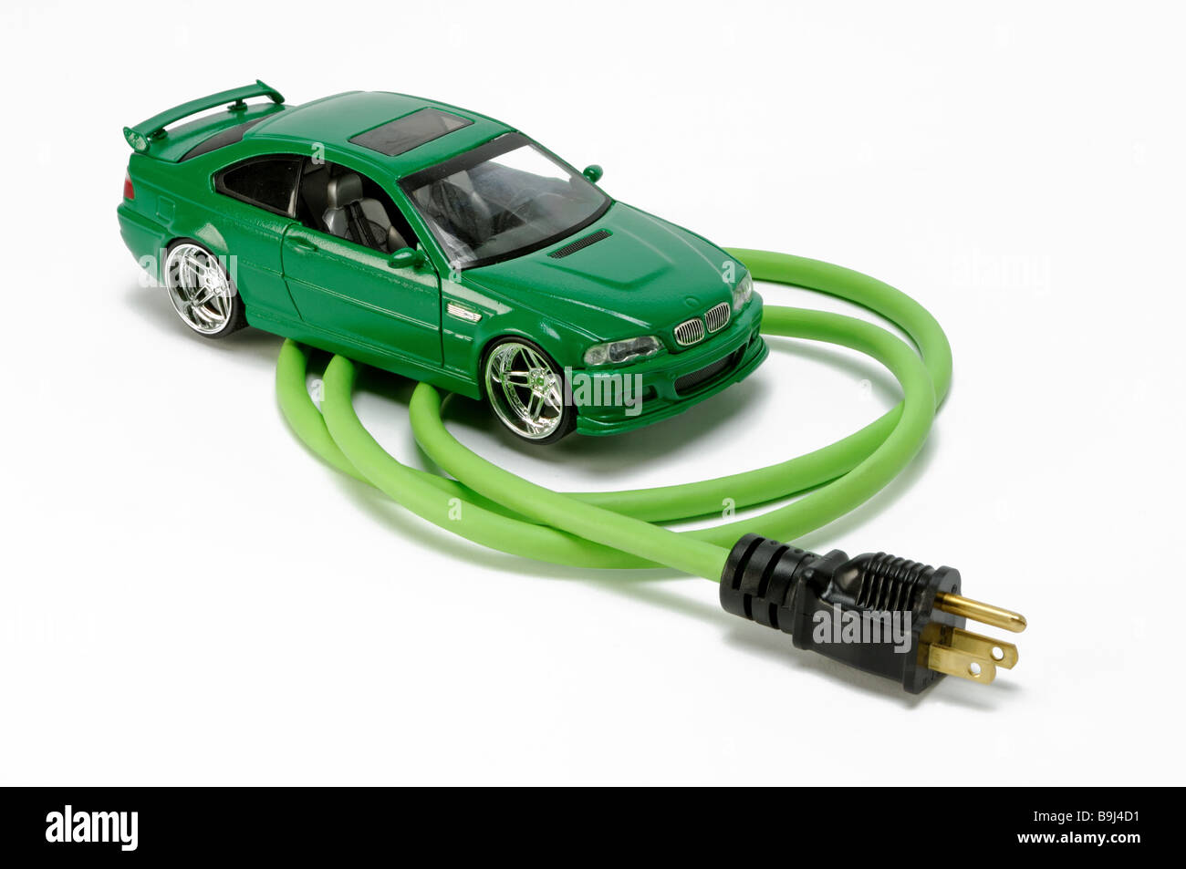 A green automobile vehicle car with a green electrical extension power cord section with one plug - Stock Image