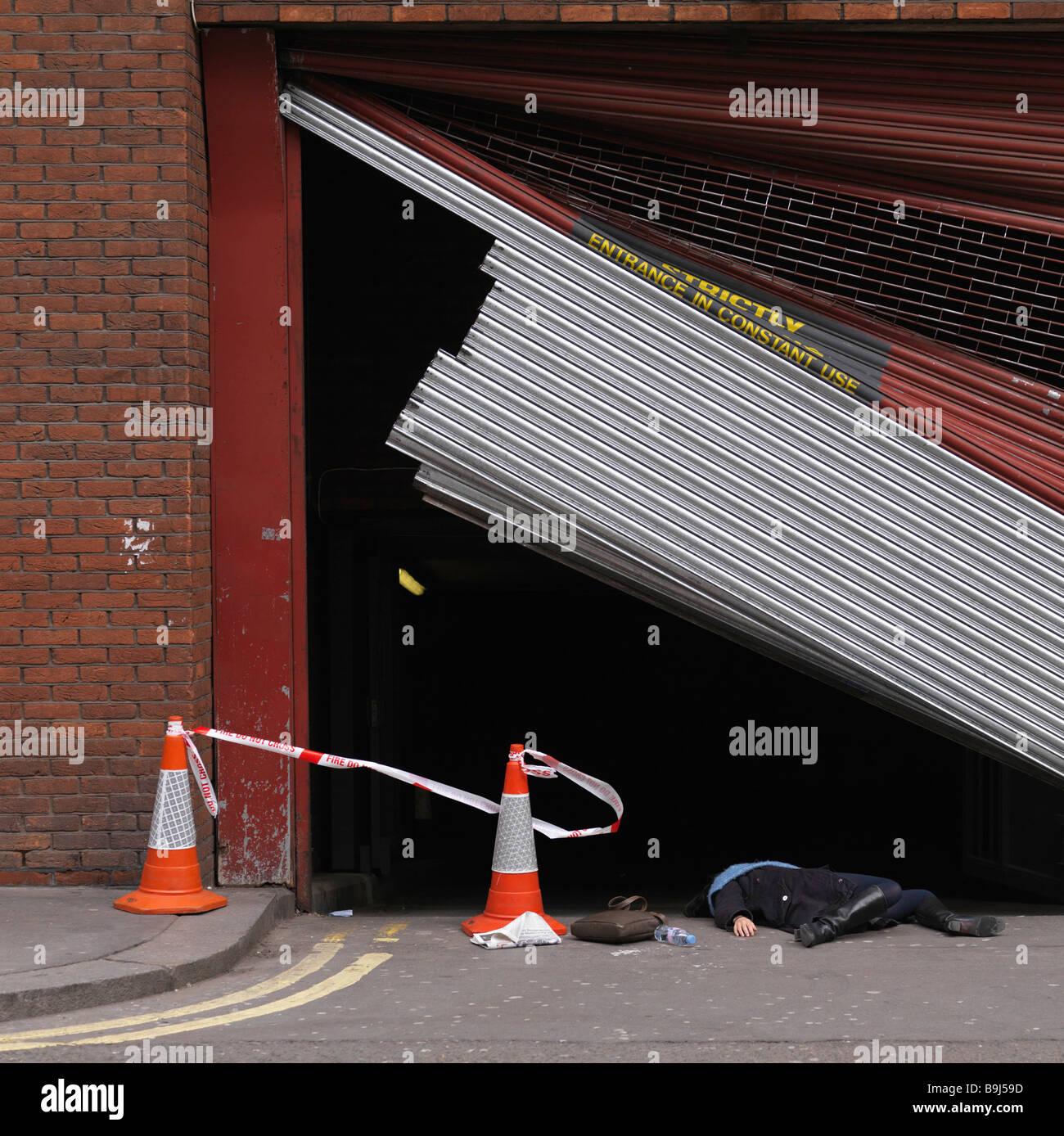 Woman lying underneath broken shutter - Stock Image