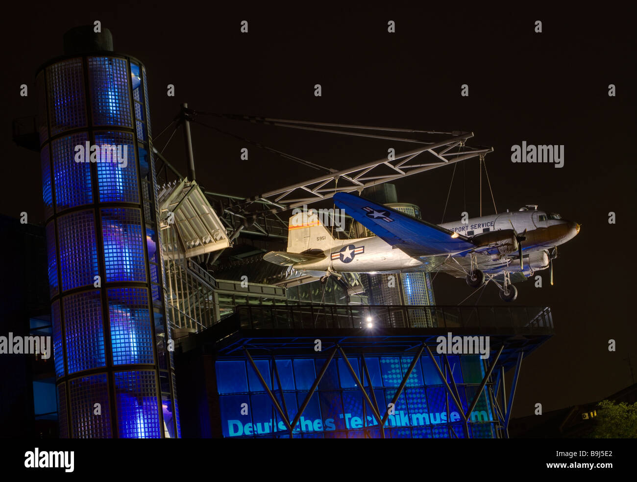 Night shot of the front of the German Technology Museum, Deutsches Technik Museum, with Raisin Bomber or Candy Bomber, - Stock Image