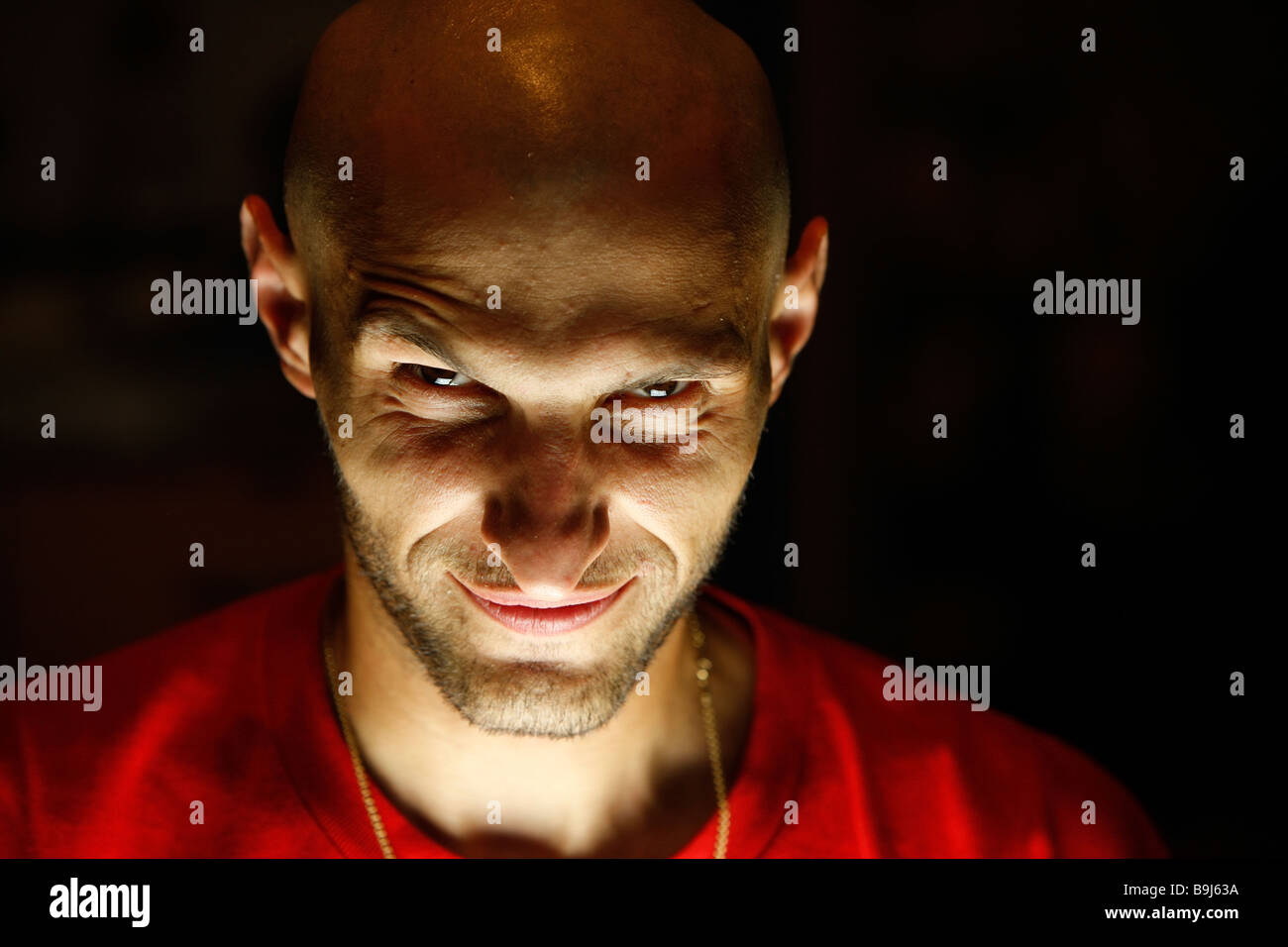 terrifying looking man with a smirk oh his face looking at the camera - Stock Image