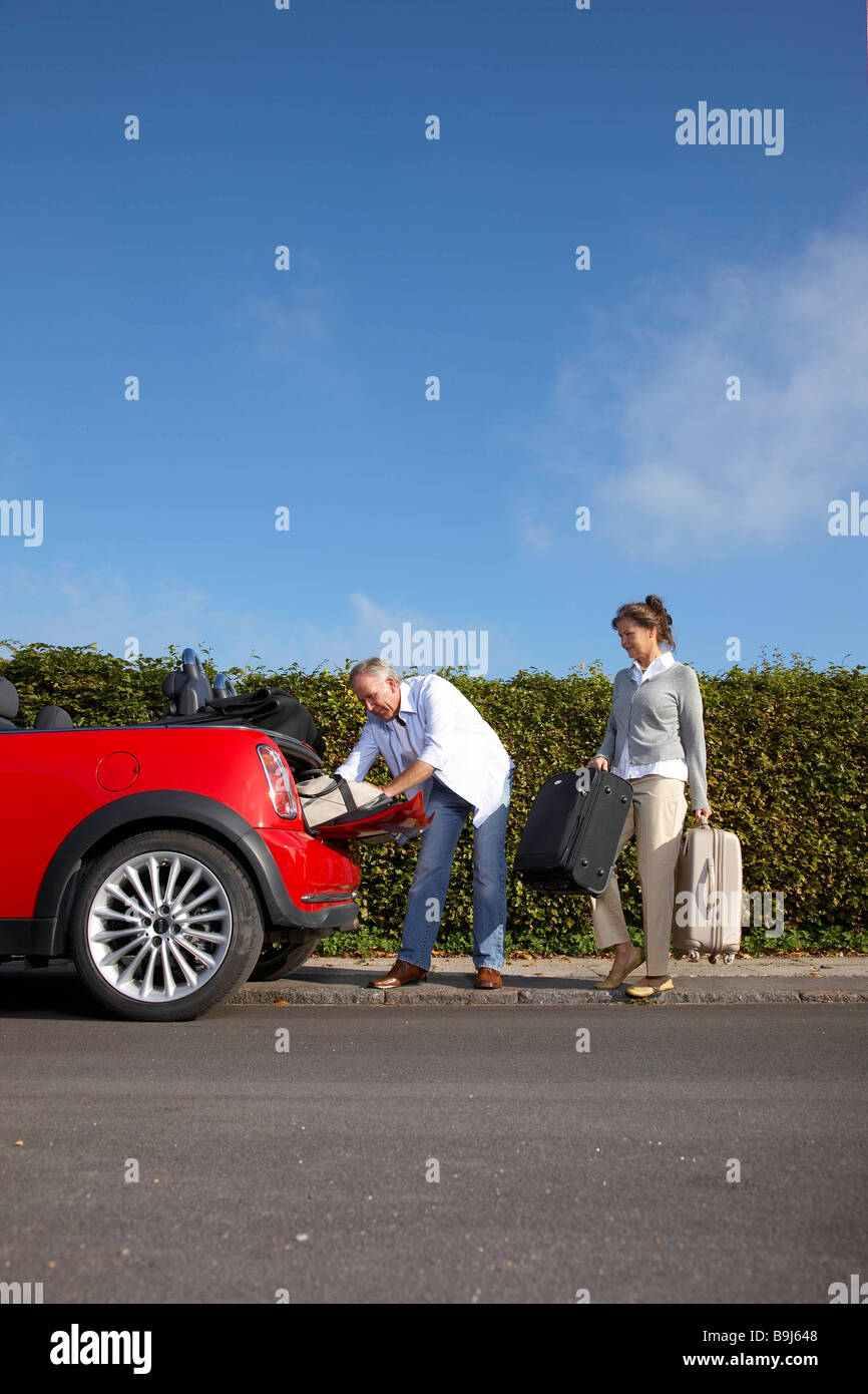 Mature couple putting bags into car - Stock Image