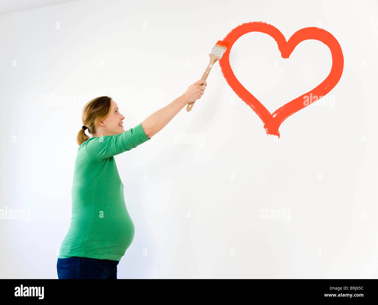 Pregnant woman painting nursery - Stock Image