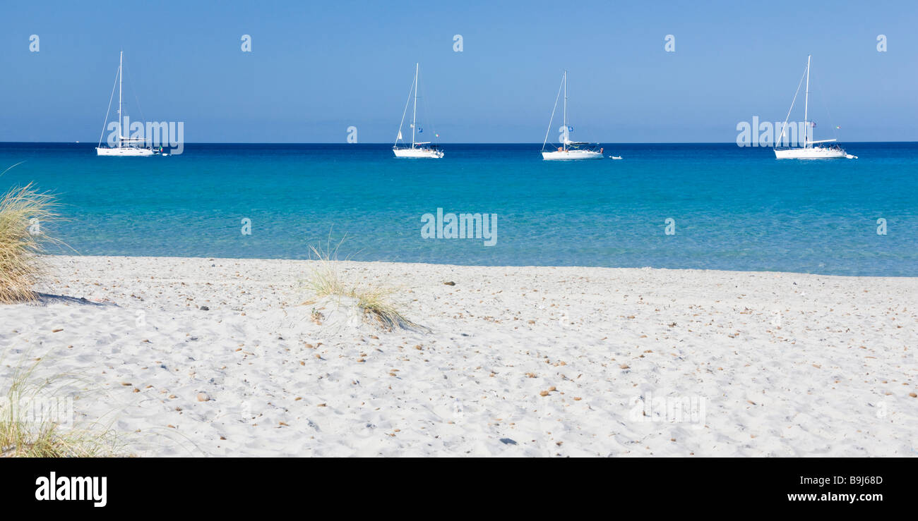 Boots anchored in front of dune beach of Porto Pino, Sardinia, Southern Coast, Italy, Europe Stock Photo
