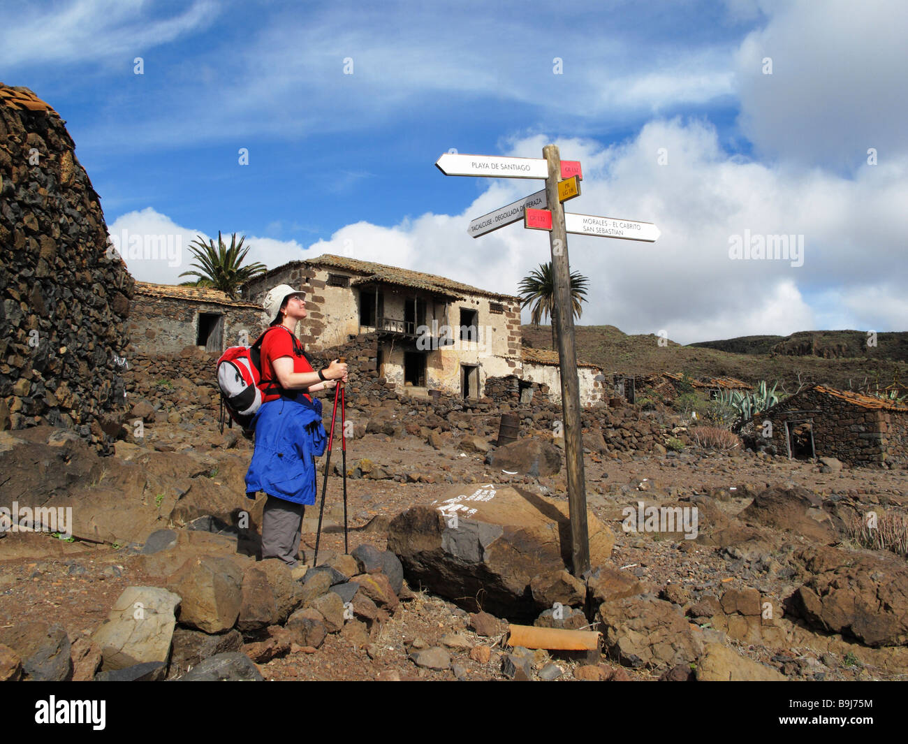 Hiker, signpost and deserted houses in Contreras near Playa Santiago, La Gomera, Canary Islands, Spain, Europe - Stock Image