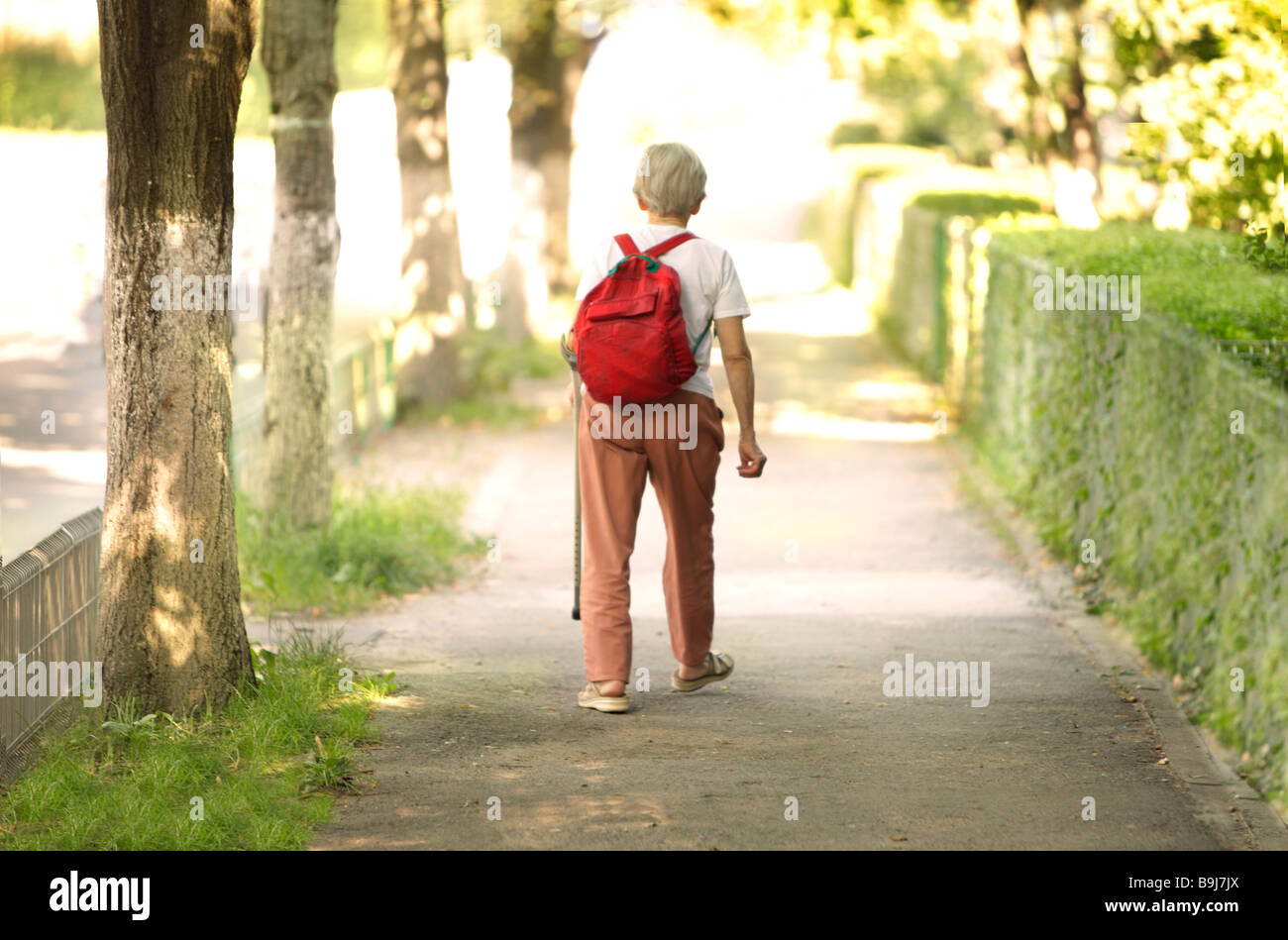 elderly woman walking in a green park with a red back pack on her shoulders - Stock Image