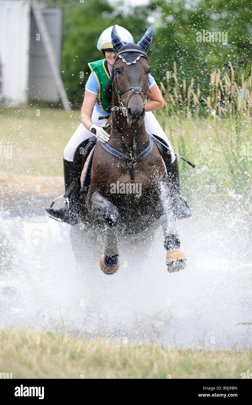 Horse galloping through the water, eventing, Tournament Grosskayna, Saxony-Anhalt, Germany, Europe - Stock Image