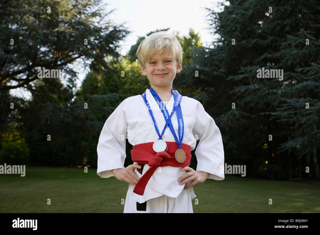 Boy in Karate Kit,  with medals - Stock Image