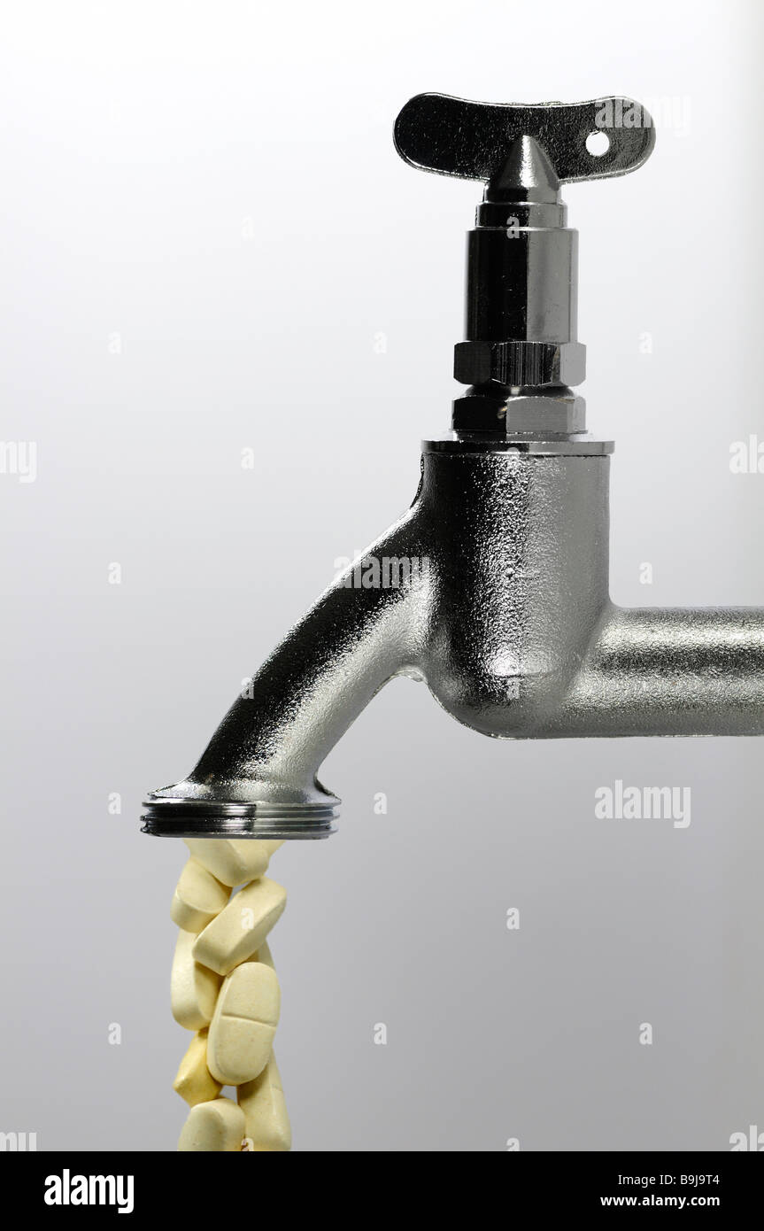 Tablets drop from water tap, symbolic of contamination of drinking water by medication, hormones, chemicals, contaminates - Stock Image