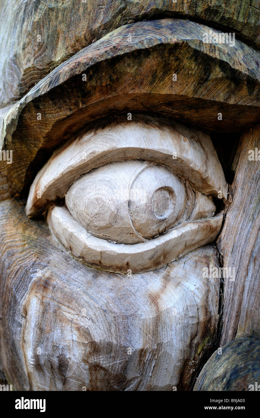 Carved eye on a weathered tree - Stock Image