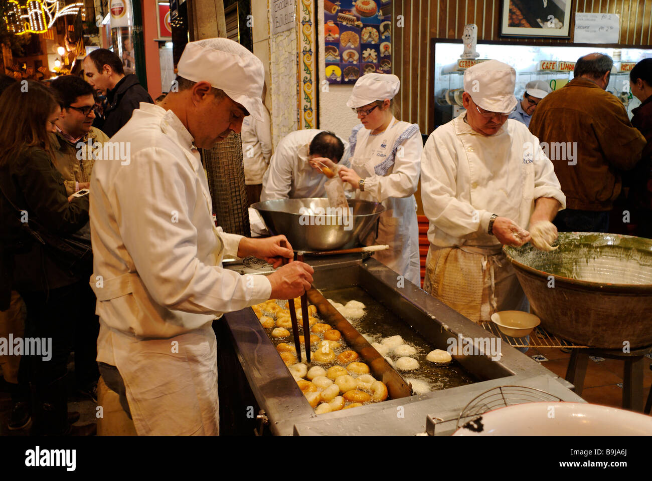 People cooking Spanish donuts Buñuelos traditionally eaten during Las Fallas festival with hot chocolate Valencia - Stock Image