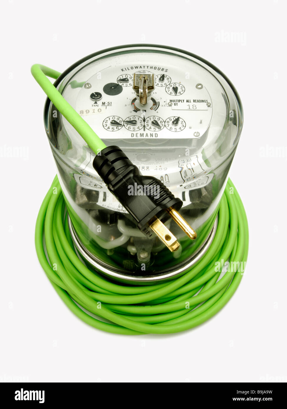 Electric power meter wrapped by a green electrical extension cord and plug - Stock Image