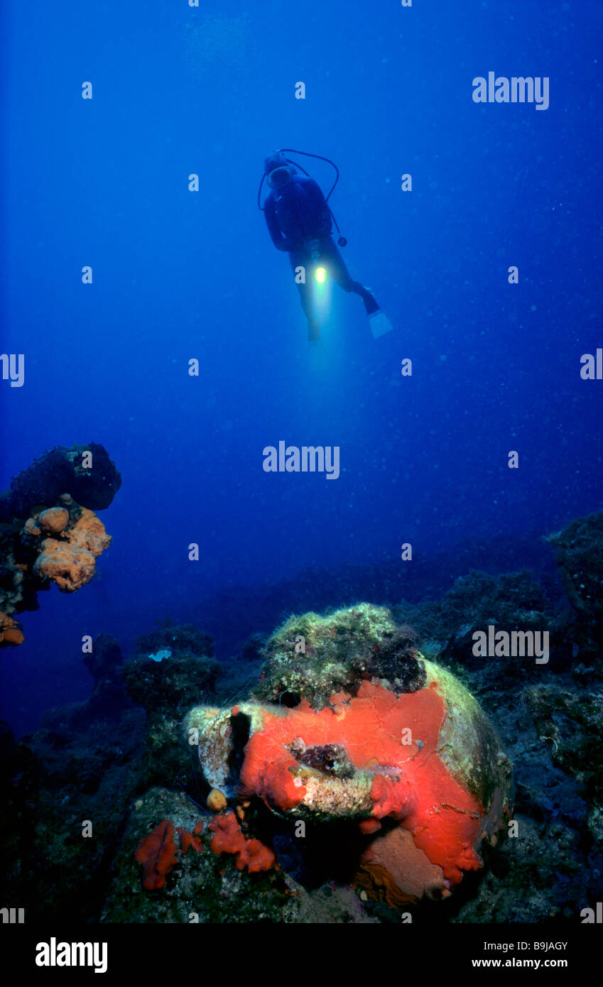 Scuba diver swimming above an Amphora overgrown with a red sponge, Mediterranean Sea, Turkey - Stock Image