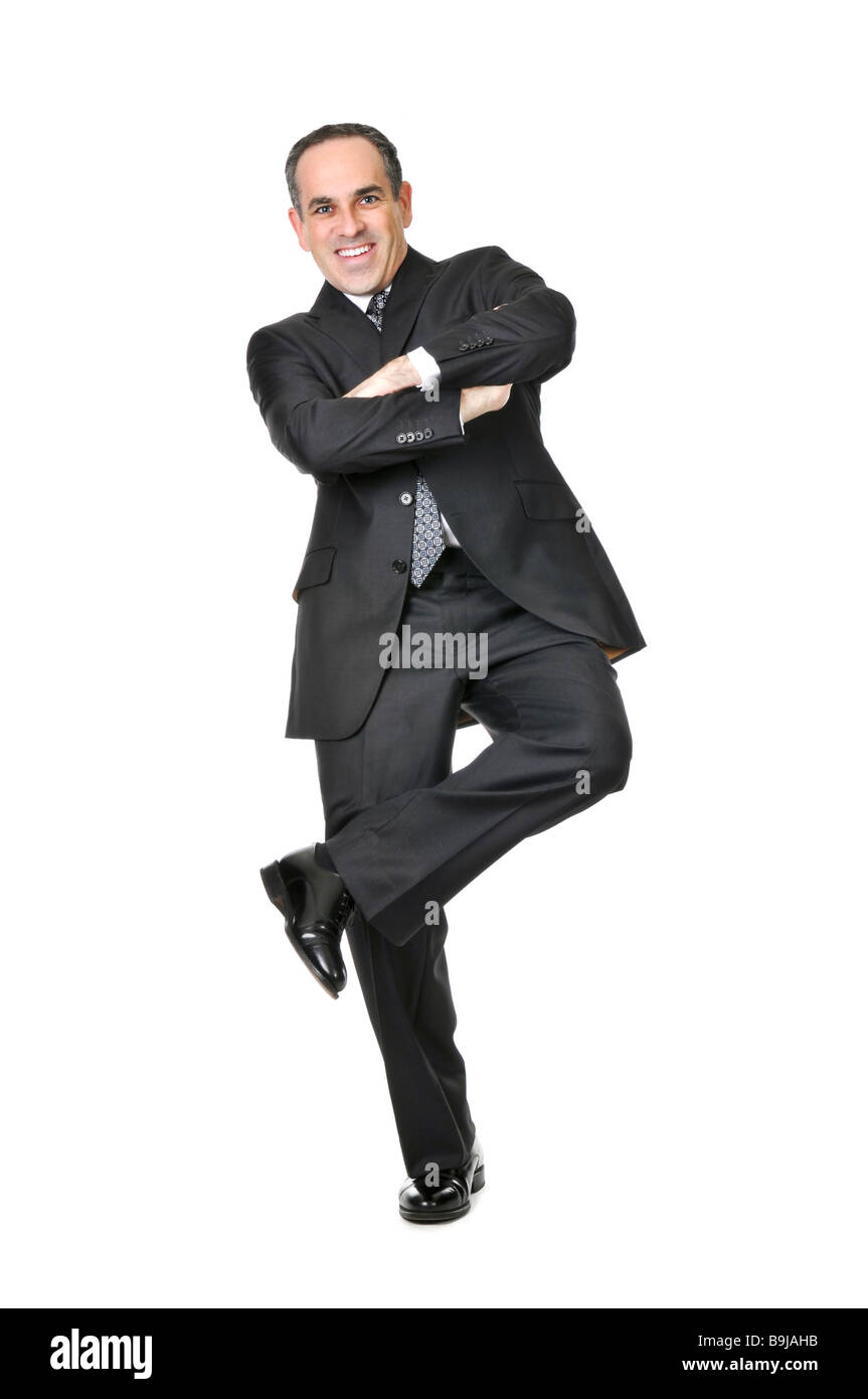 Happy businessman in a suit standing on one leg isolated on white background - Stock Image