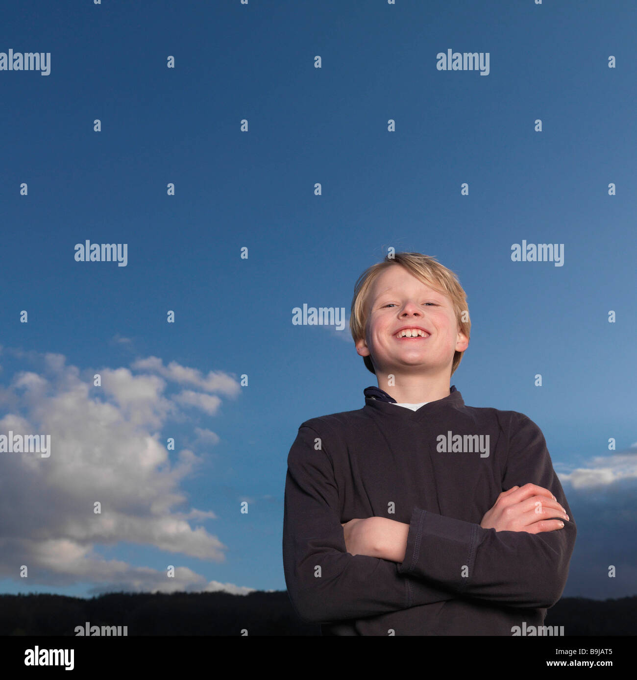 Boy standing with arms crossed,  smiling Stock Photo
