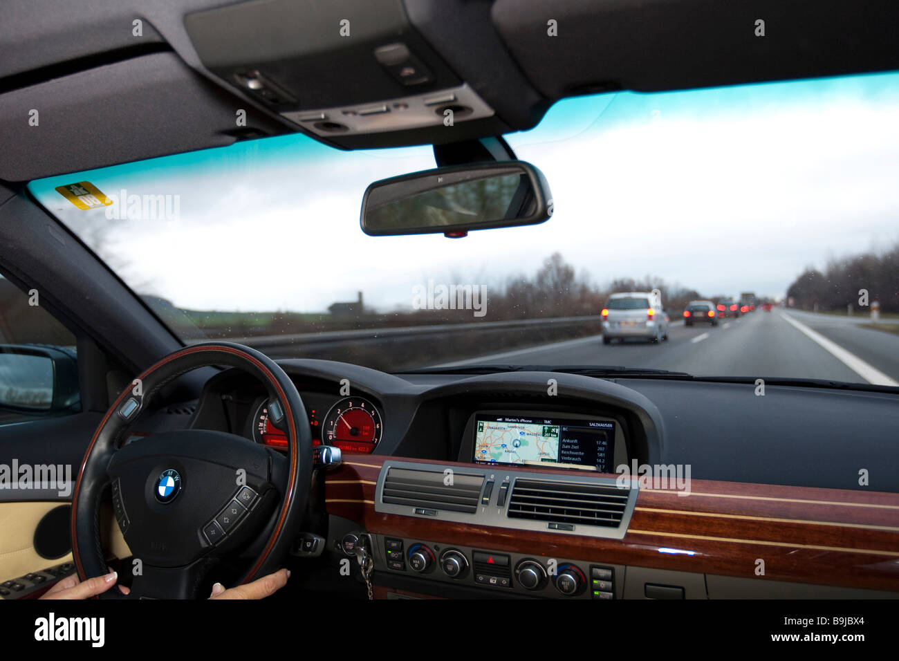 Woman driving a car with a navigation assistant on the right lane of a motorway - Stock Image
