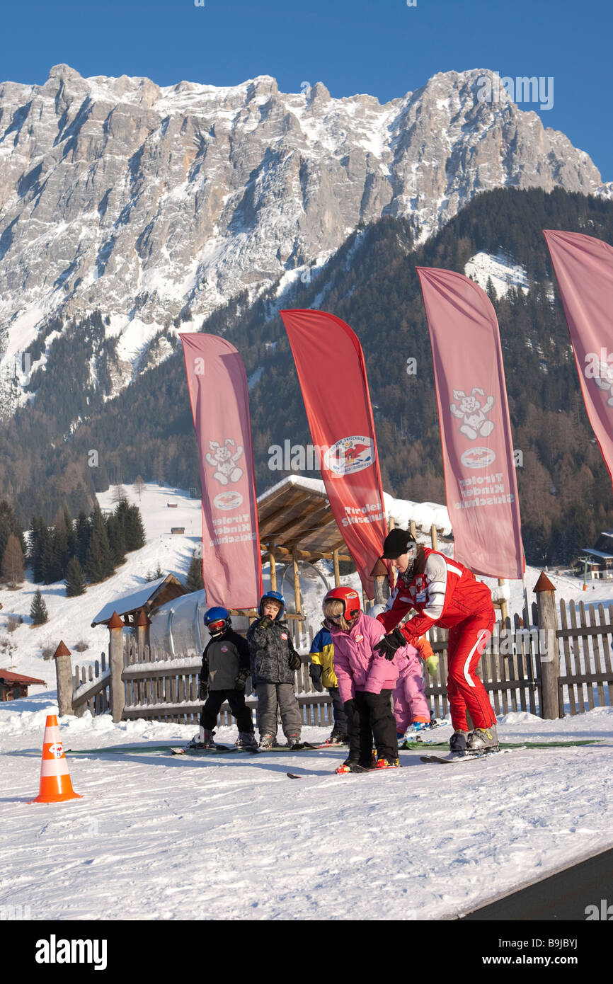 Children being taught by a ski instructor in a beginners course in a ski school in front of Zugspitze mountain, - Stock Image